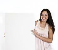 Mujer que lleva a cabo una muestra blanca en blanco Foto de archivo libre de regalías