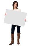 Mujer que lleva a cabo una muestra blanca en blanco imagenes de archivo