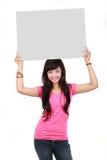 Mujer que lleva a cabo a una tarjeta en blanco Fotos de archivo libres de regalías