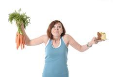 Mujer que lleva a cabo zanahorias y la nutrición sana de la torta Foto de archivo libre de regalías