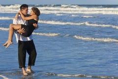 Mujer que lleva del hombre en abrazo romántico en la playa imágenes de archivo libres de regalías