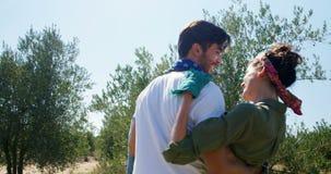 Mujer que lleva del hombre en la granja verde oliva 4k almacen de metraje de vídeo