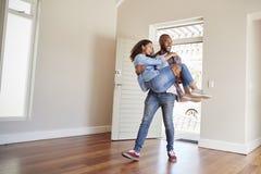 Mujer que lleva del hombre sobre el umbral de la entrada en nuevo hogar fotografía de archivo libre de regalías