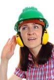 Mujer que lleva el casco y los auriculares protectores Imagen de archivo