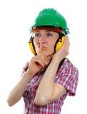Mujer que lleva el casco y los auriculares protectores Fotos de archivo