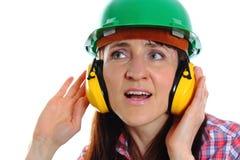 Mujer que lleva el casco y los auriculares protectores Foto de archivo