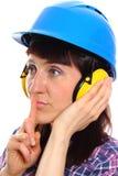 Mujer que lleva el casco y los auriculares protectores, muestra del silencio Imagenes de archivo