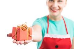 Mujer que lleva el delantal rojo que da dando el regalo envuelto de ofrecimiento o fotografía de archivo libre de regalías