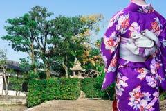 Mujer que lleva el kimono japonés tradicional que camina al templo en Kyoto, Japón imagenes de archivo
