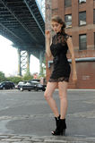 Mujer que lleva el minidress negro que se coloca debajo del puente de Manhattan Imagen de archivo libre de regalías