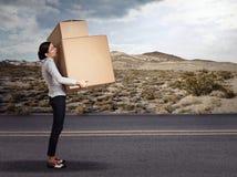Mujer que lleva el paquete grande pesado de la caja Foto de archivo libre de regalías