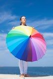 Mujer que lleva el paraguas iridiscente Imagen de archivo libre de regalías