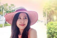 Mujer que lleva el sombrero de paja rosado con la expresión de feliz fotos de archivo