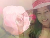 Mujer que lleva el sombrero de paja rosado con la expresión de feliz con rosa foto de archivo libre de regalías