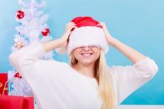 Mujer que lleva el sombrero de Papá Noel que la cubre los ojos Imagen de archivo