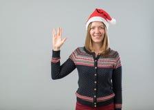 Mujer que lleva el sombrero de Papá Noel que muestra el saludo de Vulcan Foto de archivo