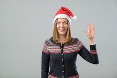 Mujer que lleva el sombrero de Papá Noel que muestra el saludo de Vulcan Imagen de archivo libre de regalías