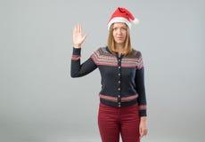 Mujer que lleva el sombrero de Papá Noel que muestra el saludo de Vulcan Foto de archivo libre de regalías