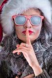 Mujer que lleva el sombrero y las gafas de sol de Santa Claus Imagen de archivo