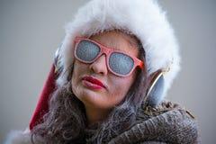 Mujer que lleva el sombrero y las gafas de sol de Santa Claus que escuchan la música Imagenes de archivo