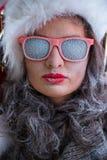Mujer que lleva el sombrero y las gafas de sol de Santa Claus que escuchan la música Foto de archivo libre de regalías