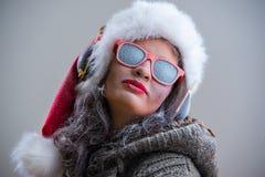Mujer que lleva el sombrero y las gafas de sol de Santa Claus que escuchan la música Fotografía de archivo libre de regalías