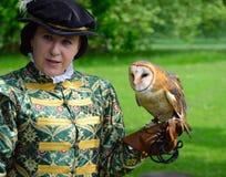 Mujer que lleva el traje isabelino con la lechuza común en la mano con guantes Foto de archivo libre de regalías