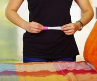 Mujer que lleva el vestido negro que se coloca que detiene la prueba casera del embarazo en el frente, tocando su propio estómago Imágenes de archivo libres de regalías