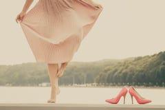 Mujer que lleva el vestido rosa claro largo en el embarcadero Imagenes de archivo