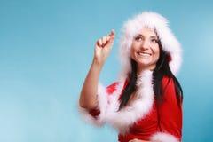 Mujer que lleva gesto de medición del finger del traje de Papá Noel en azul Fotos de archivo