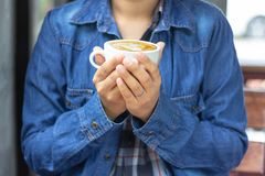 Mujer que lleva la camisa azul y la mano de la mezclilla que sostienen una taza de café con leche plano fotografía de archivo libre de regalías