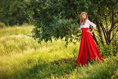 Mujer que lleva la falda roja que se coloca debajo del árbol Foto de archivo libre de regalías