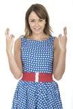 Mujer que lleva la polca azul Dot Dress Fingers Crossed Fotografía de archivo libre de regalías