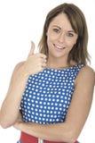 Mujer que lleva la polca azul Dot Dress Thumbs Up Fotos de archivo libres de regalías
