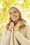 Mujer que lleva la ropa caliente debajo de Autumn Tree Foto de archivo libre de regalías