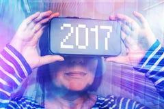 Mujer que lleva las auriculares de la realidad virtual con el número 2017 Fotos de archivo libres de regalías