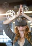 Mujer que lleva las auriculares de la realidad virtual de VR con los orbes del interfaz Fotografía de archivo