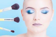Mujer que lleva maquillaje profesional y tres cepillos Fotos de archivo libres de regalías