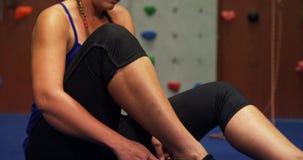 Mujer que lleva su calzado en el gimnasio bouldering 4k metrajes