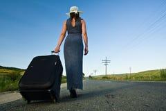 Mujer que lleva un bolso en la mujer que lleva un bolso pesado Imagenes de archivo