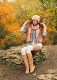 Mujer que lleva un casquillo y una bufanda de punto en parque Imagen de archivo libre de regalías