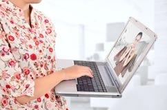 Mujer que lleva un ordenador portátil y que hace compras en línea Fotos de archivo libres de regalías