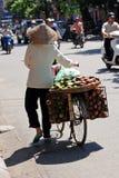 Mujer que lleva una cesta de fruta en Hanoi Fotografía de archivo