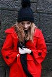 Mujer que lleva una chaqueta y un sombrero rojos del pom del pom Fotografía de archivo