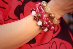 Mujer que lleva una joyería roja de la camisa y de la pulsera Imagen de archivo