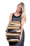 mujer que lleva una pila pesada de libros Imagenes de archivo