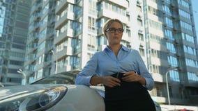 Mujer que llora cerca del automóvil, dificultades financieras, incapacidad para pagar préstamo de coche metrajes
