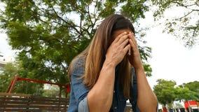 Mujer que llora en un parque almacen de metraje de vídeo