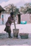 Mujer que machaca el mijo, África, Namibia fotos de archivo