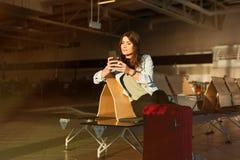 Mujer que manda un SMS antes de conseguir en el avión Imagenes de archivo